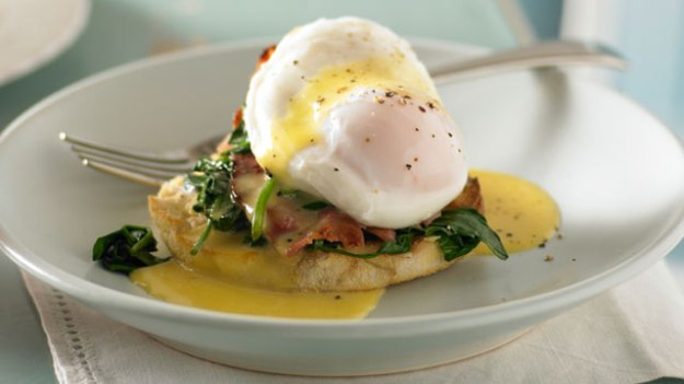 Eggs Benedict with spinach and bacon served on an English muffin