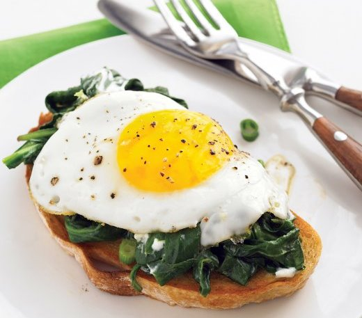 Home-made poached egg on a bed of garlic spinach served on GF toast