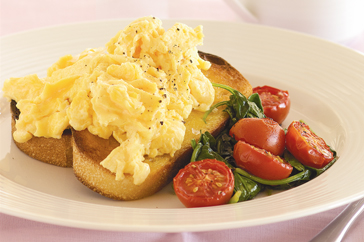 Home-made scrambled eggs with spinach and tomatoes served on GF toast
