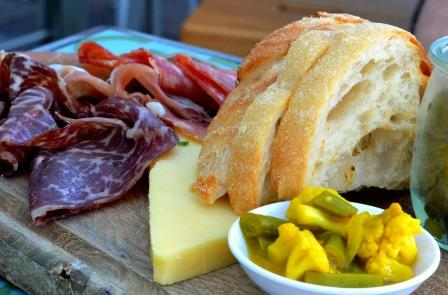 Picnic goodies - selection of cold meats, cheeses, bread and pickle