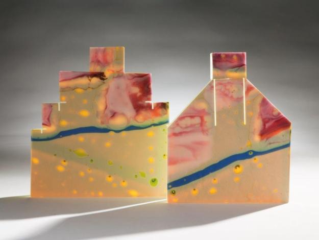 (Two small houses) Judi Elliott. On our Street 1.  Height 19cm x 19cm. Cast cut and assembled glass. On our street 2, Height 19cm x 15cm. Cast, cut and assembled glass. Image credit: Rob Little.