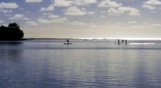 Early morning paddle boarders with Koromiri Motu on the left